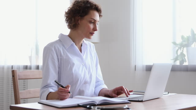 Young female nurse writing notes using laptop at workplace Young female nurse writing notes using laptop at workplace desk. Woman professional doctor wearing white coat working on computer checking appointments, doing research or report in hospital office. general view stock videos & royalty-free footage