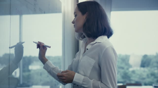 young female office worker in white shirt is writing on glass whiteboard. - apprendista video stock e b–roll