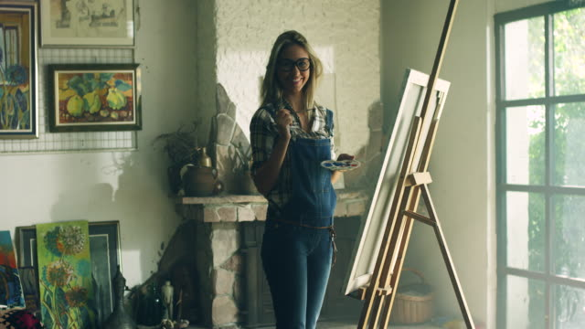 Young female painter at the artist's studio video