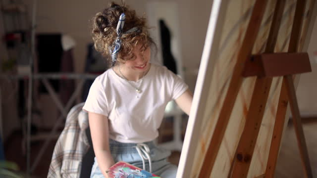 Young female painter working video