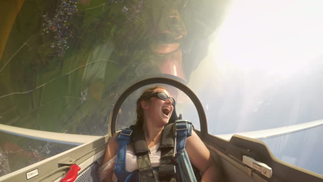 Video LD Young female passenger in the glider having a great time as the pilots turns the glider upside down a few times