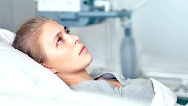 Young female patient lying in a hospital room. Sad and upset woman thinking about life in a modern clinic Young female patient lying in a hospital room. Sad and upset woman thinking about life in a modern clinic. hospital bed stock videos & royalty-free footage