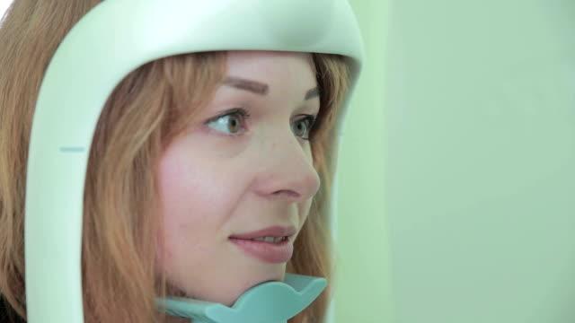 目の検査で若いメスの患者。明るいモダンなクリニックでの検眼医で治療 - 検眼医点の映像素材/bロール