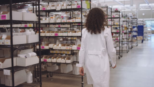 4K UHD: Young female pharmacist walking past aisles of medications video