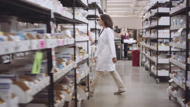 4K UHD: Young female pharmacist walking through aisles of medications 4K UHD: Young multi-ethnic female pharmacist walking through aisles of medications storage room stock videos & royalty-free footage