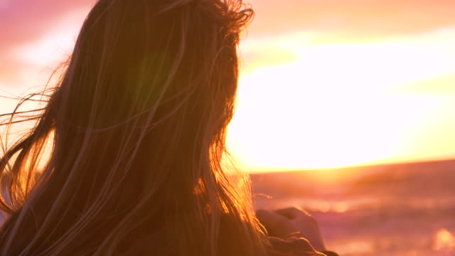 CLOSE UP: Young female photographer looking at the beautiful evening sun and sea