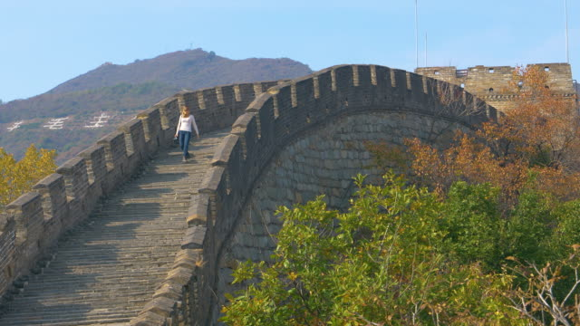 Young female photographer walks down the ancient stairs on top of the Great Wall