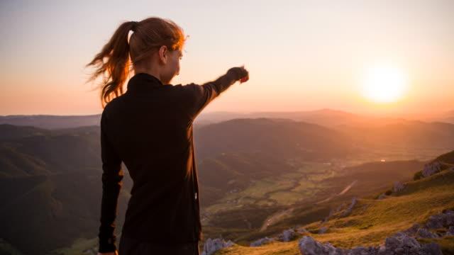 Jeune femelle pointant à belle vue du coucher de soleil à flanc de montagne - Vidéo