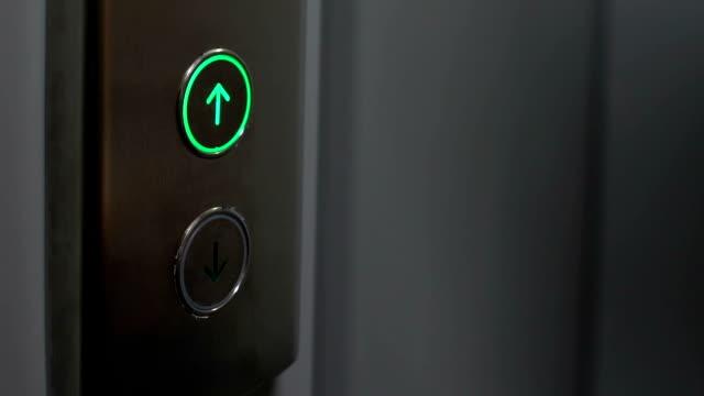 giovane donna premendo il pulsante in ascensore, edificio moderno per uffici, casa - ascensore video stock e b–roll
