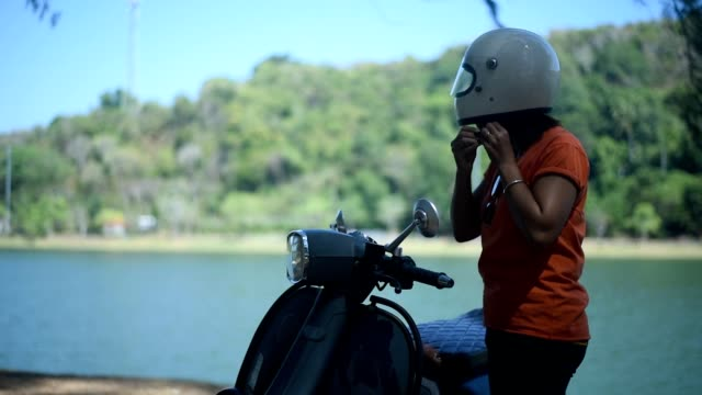 vídeos de stock e filmes b-roll de young female putting on helmet near her scooter, beside the lake. - helmet motorbike