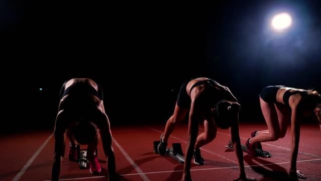 ランニング トラック スタート ラインでスプリントする準備ができてのスマートウォッチと若い女性ランナーの選手 - 陸上競技点の映像素材/bロール