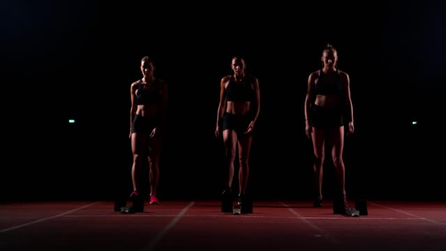 Young female runner athlete with smartwatch ready to sprint at running track starting line