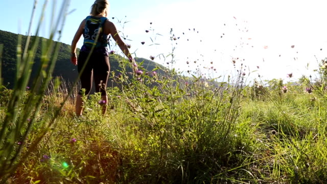Young female runner pauses on hilltop field First person perspective pedal pushers stock videos & royalty-free footage
