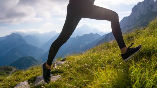 Young female runner running uphill
