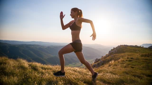 unga kvinnliga löpare utbildning i fjällen - jogging hill bildbanksvideor och videomaterial från bakom kulisserna