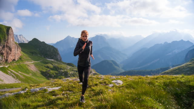 Young female runner training in the mountains video