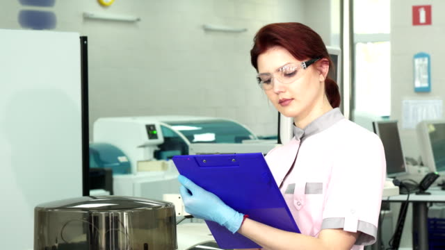 Young female scientist taking notes at the modern lab