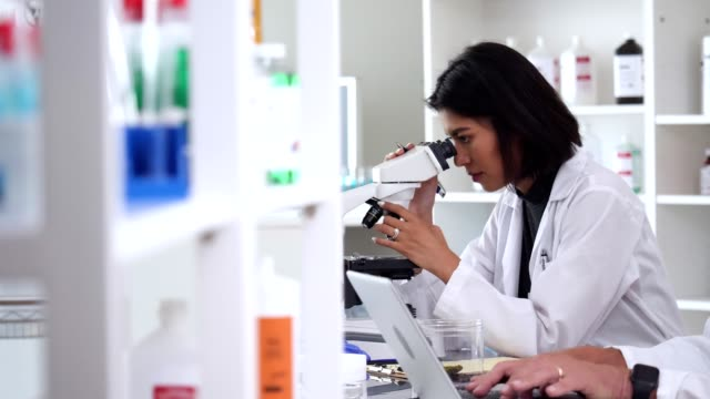 Young female scientist uses microscope in lab