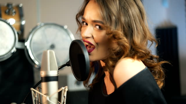 Young female singer recording album in the professional studio. Young female singer recording album in the professional studio. Woman singing a song in music recording studio. red lipstick stock videos & royalty-free footage