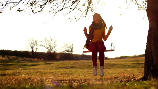 Young Female Sitting on Swing Autumn Nature video