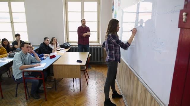 junge studentinnen, die mathematik auf dem whiteboard machen - highschool stock-videos und b-roll-filmmaterial