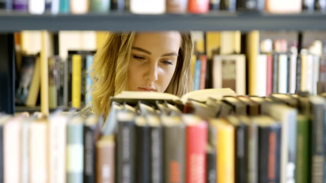 Young female student looking for book in school library video