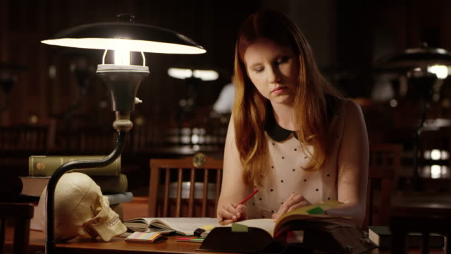 DS Young female student studying in library at night video