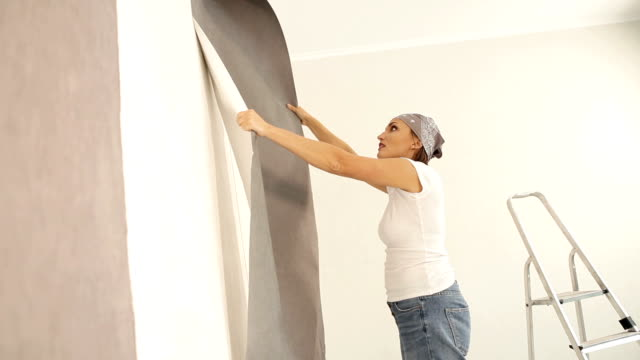 Young female takes off the old wallpaper and happy smiling. video