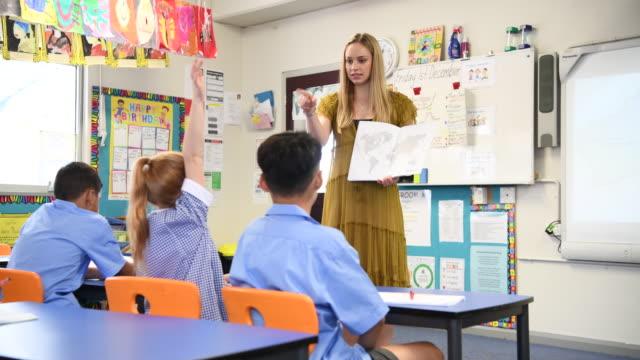 Joven maestra sosteniendo el libro y el mapa del mundo mostrando clase - vídeo