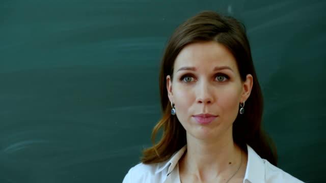 Jonge vrouwelijke leraar vertellen interessant aan de klasse in de buurt van het bord video