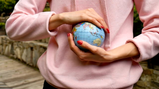 young female teenager in pink casual clothes with red manicure holding a little globe with geografical names in ukrainian cyrillic letters on it in her hands. enviromental responsibility concept. - sustainable living stock videos and b-roll footage