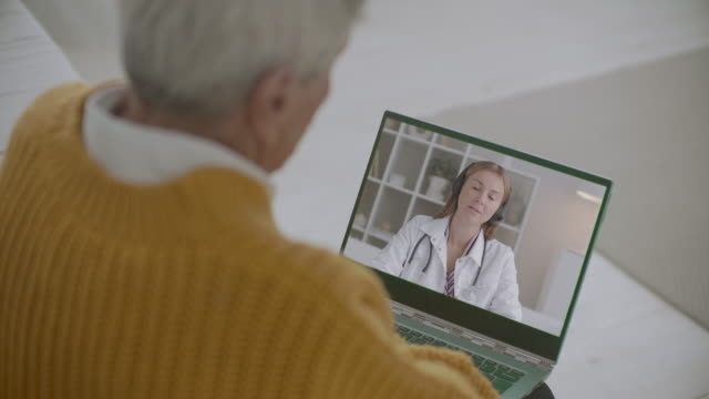 young female therapist is answering on questions of old person online, elderly man is listening and viewing her on display, telehealth