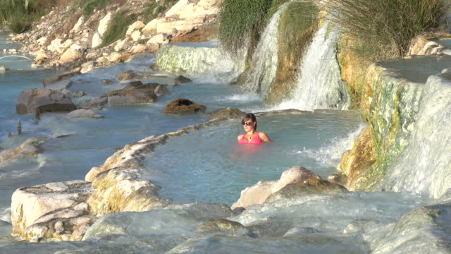 Young female tourist enjoys a relaxing hot bath in the thermal springs in Italy. Young female tourist enjoys a relaxing hot bath in the thermal springs in sunny Italy. Cheerful Caucasian woman unwinding in the picturesque geothermal pools of Tuscany. Girl bathing in outdoor spa. natural condition stock videos & royalty-free footage