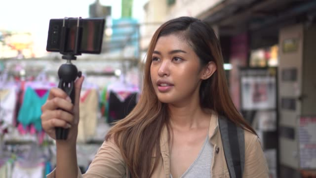 young female tourist holding a gimbal with smartphone and recording videos. travel blogger and vlogger concept - influencer стоковые видео и кадры b-roll