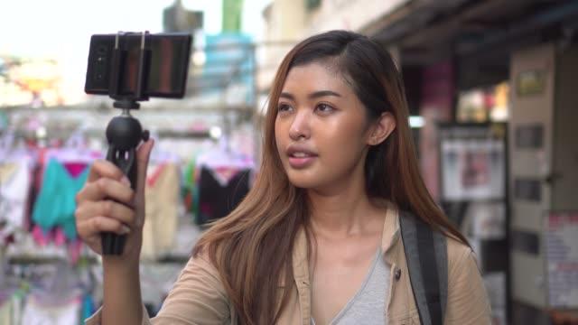 젊은 여성 관광객 스마트폰 및 녹화 비디오와 짐 벌을 들고. 여행 블로거 및 동영상 블로거 개념 - influencer 스톡 비디오 및 b-롤 화면
