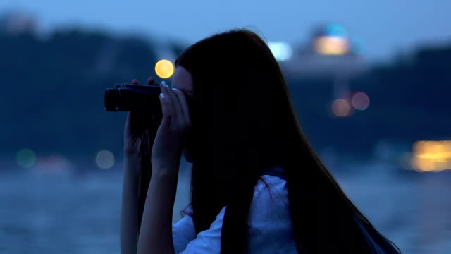 Young female tourist looking night city through binoculars, travel recreation
