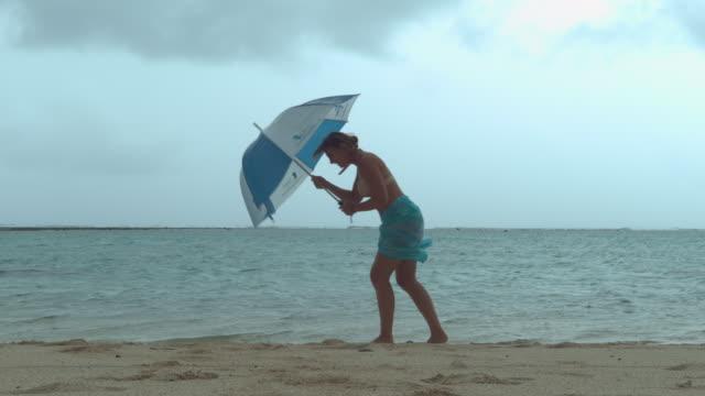 vídeos de stock e filmes b-roll de young female tourist struggles to walk down the sandy beach in the strong wind. - guarda chuva