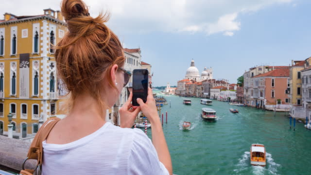 Young female tourist taking photos of Venice, Italy video