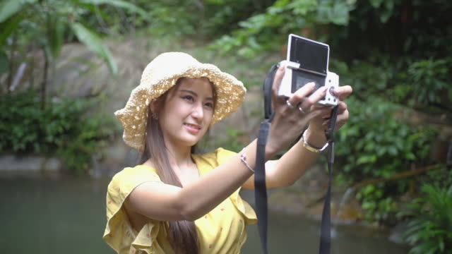 Young female tourists in yellow dress taking a selfie by the camera in the garden.