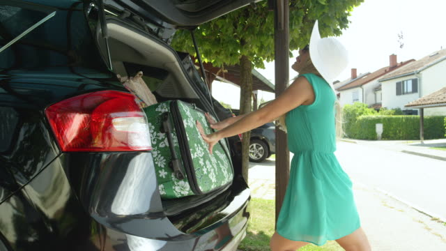 CLOSE UP: Young female tourist's luggage falls out of the back of her black SUV. CLOSE UP, LENS FLARE: Young female tourist's luggage falls out of the back of her black SUV parked in front of her home in the sunny suburbs. Heavy travel bags fall out of cheerful woman's big car. stuffed stock videos & royalty-free footage