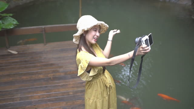 Young female tourists taking a selfie by the camera in the garden.