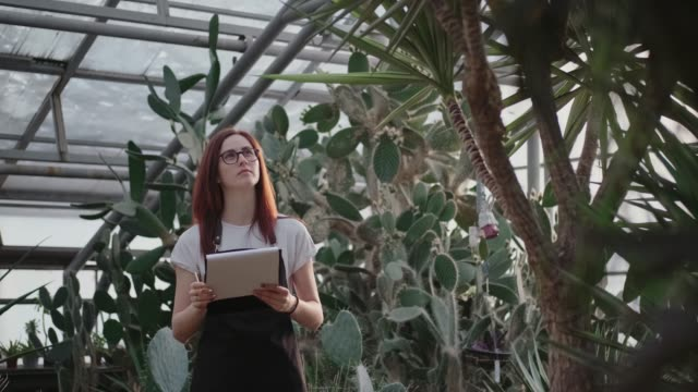 Young female trainee in botanical garden stands against a large cacti