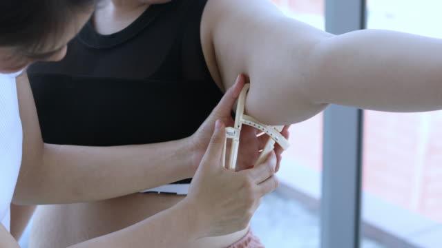 vídeos y material grabado en eventos de stock de joven entrenadora que mide la capa de construcción grande de la mujer de construcción grande con la pinza en el fitness - misa