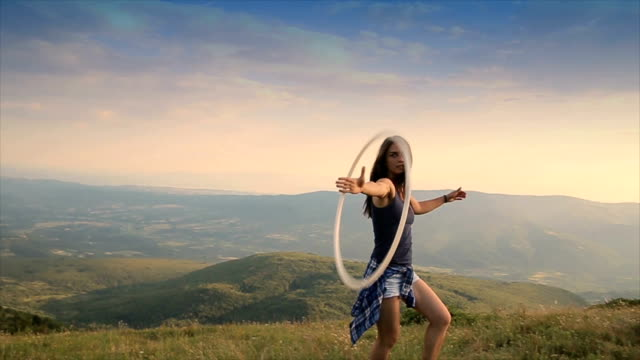 young female using a hula hop on the mountain video