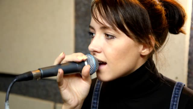 Young female vocalist with microphone singing in studio video