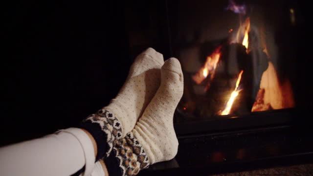 unga kvinnliga uppvärmningen hennes fötter drog med jul ornamenterade strumpor nära eldstaden. mysig jul hem konceptet slow motion footage - strumpa bildbanksvideor och videomaterial från bakom kulisserna
