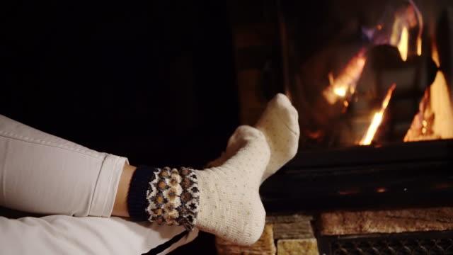 若い女性が彼女の足を地球温暖化は、暖炉のそばの装飾クリスマスの靴下を引っ張った。居心地の良いクリスマスの家コンセプト 4 k 解像度映像 - 寂しさ点の映像素材/bロール