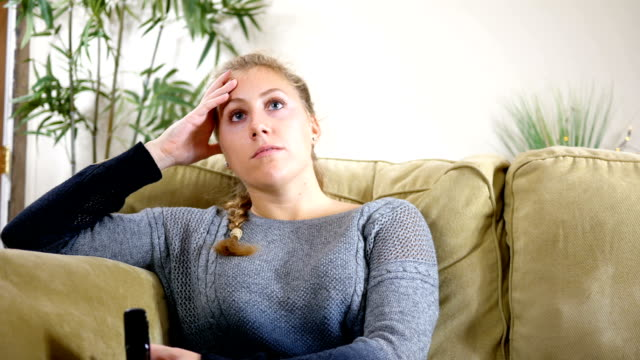 Young female watches TV in her modern living room on couch video