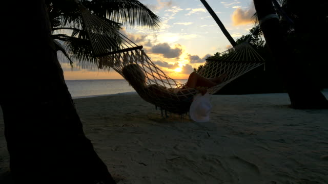 Young female watching beautiful golden sunrise while lying in hammock on exotic sandy beach video
