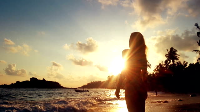 Young female watching sunset at tropical beach, stormy ocean waves washing sand video